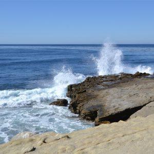 Gischt spritzt an einer Felsküste, Foto: EP